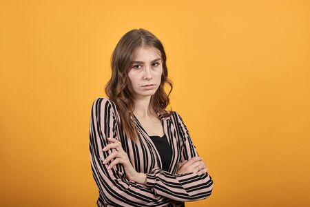 Cute Young Woman Light Brown In Striped Pink, Black Shirt On A Yellow Background, Offended Woman Put Her Hands One In Another And Is Angry. Concept Of Conflicts In The Family, Society