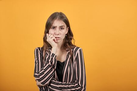 Cute Young Woman Light Brown In Striped Pink, Black Shirt On A Yellow Background, An Unsure Girl Leaned Her Chin On Hand And Hesitated. The Concept Of Discouragement, Confusion. Banque d'images