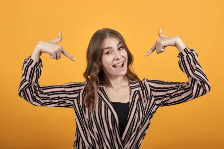 Cute Young Woman Light Brown In Striped Pink, Black Shirt On A Yellow Background, Happy Girl Smiles And Points At Herself With Her Forefinger. The Concept Of Confident, Successful People