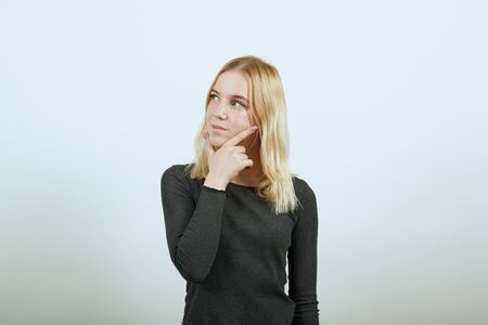 Young Blonde Woman In Black Sweater On White Background, Dreamy Girl Touches Her Chin And Thinks. The Concept Of Smart People, Intellectuals, Elite Of Society