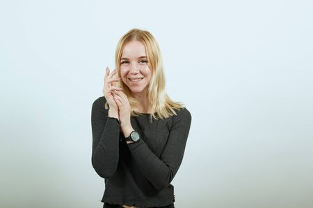 Young Blonde Woman In Black Sweater On White Background, Gentle Look Of A Girl, Put The Palms Of Her Hands Together. Concept Of Nice, Kind And Sincere People