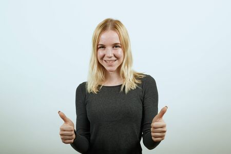 Young Blonde Woman In Black Sweater With Stylish Watch On White Background, Happy Attractive Girl Smiling, Raised Her Thumbs Fingers Up. The Concept Of Positive, Peaceful, Sincere People. Foto de archivo