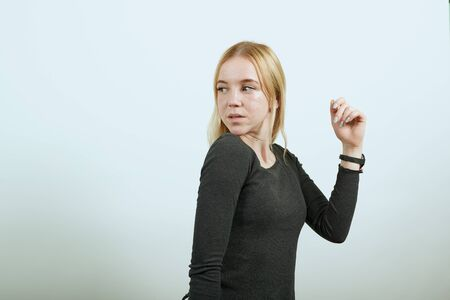 Young Blonde Woman In Black Sweater With Stylish Watch On White Background, Surprised Attractive Girl Reacts To The Circumstances With A Look. Concept Of Shocked People, Surprises Stockfoto