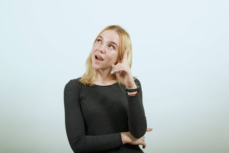Young Blonde Woman In Black Sweater With Stylish Watch On White Background, Conceived Girl Raised Forefinger Up, Thinks Of A New Idea. The Concept Of Smart And Attractive People Stockfoto
