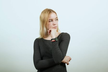 Young Blonde Woman In Black Sweater With Stylish Watch On White Background, Focused Girl Holds Hand To Her Chin. Languishing Look. The Concept Of Smart And Purposeful People.
