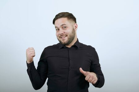 Young Bearded Dark Haired Man In Black Stylish Shirt On White Background, Sly Male Points Fingers At Opponent. The Concept Audacity And Confidence Of People 版權商用圖片