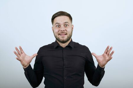 Young Bearded Dark Haired Man In Black Stylish Shirt On White Background, Surprised Male Holding Hands Wide. The Concept Of Unpredictability, Pleasant Shock