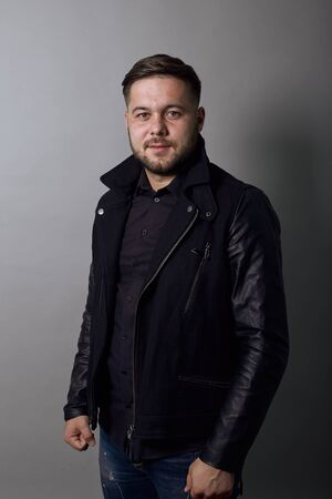 Young Bearded Dark Haired Man In Black Stylish Shirt, Jacket On Gray Background, Confident Male Looks Straight. The Concept Leadership, Success And Achievement Of Goals