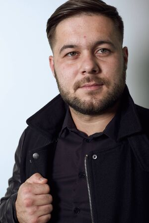 Young Bearded Dark Haired Man In Black Stylish Shirt, Jacket On Gray Background, Confident Male Holds Hands On Edge Clothing And Poses For Camera. Concept Of The Top Models. Close Up Stock Photo