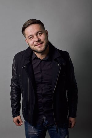Young Bearded Dark Haired Man In Black Stylish Shirt, Jacket On Gray Background, Happy Male Smiles Bowed His Head And Looks Straight Ahead. The Concept Of Self-Confident, Kind People