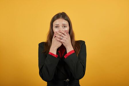 Young Attractive Brunette Woman In Black Stylish Suit, Red Shirt On Yellow Background, Shocked, Scared Woman Covered Mouth With Her Hands. The Concept Of Fear And Distrust, Surprise In People