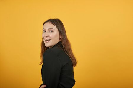 Young Attractive Brunette Woman In Black Stylish Suit, Red Shirt On Yellow Background, Surprised Girl Turned Sideways And Reacts To Surprise. The Concept Of Confused People