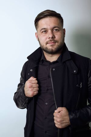 Young Bearded Dark Haired Man In Black Stylish Shirt, Jacket On Gray Background, Confident Male Holds Hands On Edge Clothing And Poses For Camera. Concept Of The Top Models
