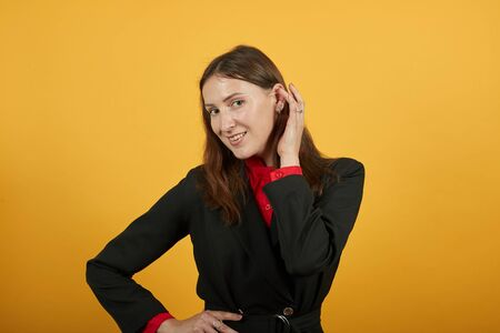Young Attractive Brunette Woman In Black Stylish Suit, Red Shirt On Yellow Background, Cute Female Holds Hand Near Her Ear And Listens. The Concept Of Eavesdropping On People, Gossip