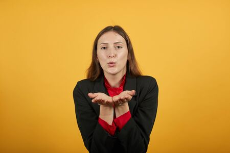 Young Attractive Woman Brunette In Black Stylish Suit, Red Shirt On Yellow Background, Cute Female Holds Palms Hands To Her Face And Makes An Air Kiss. The Concept Of People Who Love, Seduction 免版税图像