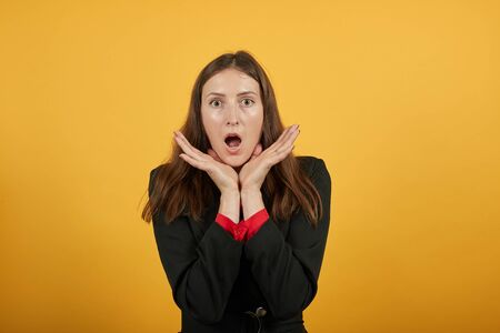 Young Attractive Brunette Woman In Black Stylish Suit, Red Shirt On Yellow Background, Shocked, Put Chin In Palms Her Hands And Is Surprised. The Concept Of Scared, Puzzled People