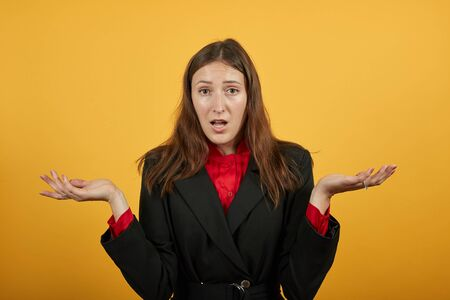 Young Attractive Brunette Woman In Black Stylish Suit, Red Shirt On Yellow Background, Confused Female Holds Hands Wide, Turned Her Palms Up. The Concept Of Shocked People Who Are Upset