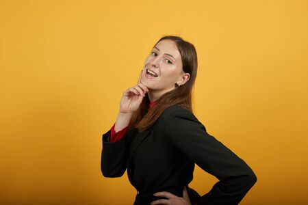 Young Attractive Brunette Woman In Black Stylish Suit, Red Shirt On Yellow Background, Sure Female Touches Hand To His Chin And Posing For Camera. The Concept Of Posing A Model 版權商用圖片