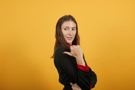 Young Attractive Brunette Woman In Black Stylish Suit, Red Shirt On Yellow Background, Sly Female Shows Thumb Finger In A Certain Direction. Concept Guilt Of The People, To Blame
