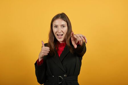 Young Attractive Brunette Woman In Black Stylish Suit, Red Shirt On Yellow Background, Happy Female Smile Shows Direction Forefinger. The Concept Of Happy People, Guilt