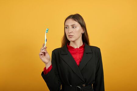 Young Attractive Brunette Woman In Black Stylish Suit, Red Shirt On Yellow Background, Centered Female Holds In Her Hands A Toothbrush To Clean The Teeth. Body Care, Dental Concept Banque d'images