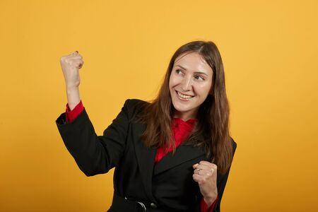 Young Attractive Brunette Woman In Black Stylish Suit, Red Shirt On Yellow Background, Happy Female Smiles Clenched Her Hands Into Fists And Raised Them Up. The Concept Of Peoples Joy, Victory