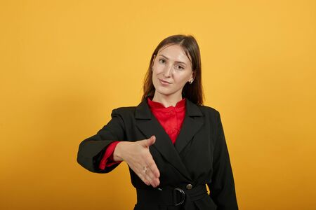 Young Attractive Brunette Woman In Black Stylish Suit, Red Shirt On Yellow Background, Friendly Female Reaches Out To Say Hello. The Concept Of Good People Etiquette, Hospitality