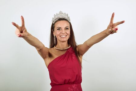 Young Attractive Brunette Woman In Red Stylish Dress, With Crown On Head On White Background, Happy Female Smiles Raised, Hands Up, Makes Sign Victory, Peace Fingers. Kindness, Friendship Of People