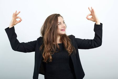 Young Attractive Woman Brunette In In Black T-Shirt And Sweater On White Background, Happy Female Smiles Raised Hands Up, Makes, Ok Sign With Her Fingers. Concept Of Happy People, Everything Is Fine