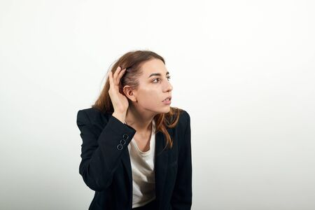 Eavesdropping, espionage, gossip, holding hand near head and looking away, what, relying on hand-ear listening the good news, trying to listen, cupping her ear. young attractive woman with brown hair