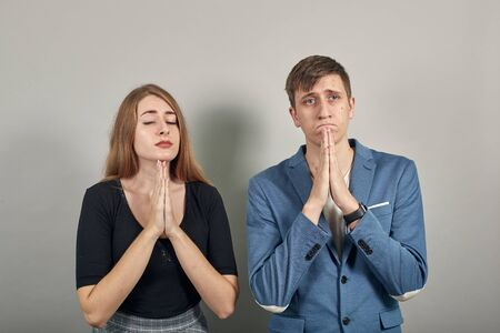 Folded hands together praying asking god for help ask implore wish upwards jesus christ. Young attractive couple boyfriend girlfriend two people, dressed black t-shirt, blue jacket, grey background
