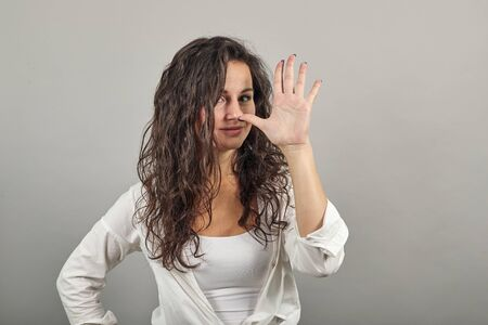 Pulling face, holding thumb to nose, teasing is putting fingers to head, makes gesture of contempt or defiance, finger up, making silly faces, crazy expressions, rude. Young attractive woman