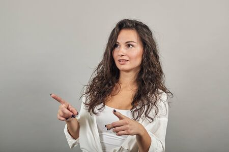 Hand pointer with forefinger pointing forward. Index finger to show direction. Means choosing, introducing too. Indicating towards. young attractive woman, dressed white blouse, with brown eyes