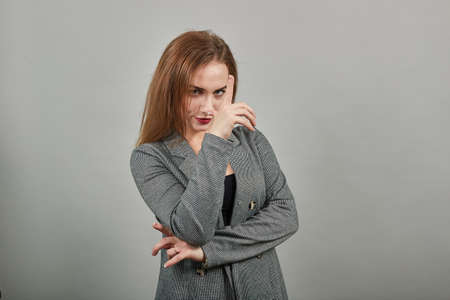 Showing loser sign, displaying dud gesture, alpha. Two fingers 2, disgust on face, negative human emotion facial expression. Young attractive woman, dressed gray jacket, with green eyes, light brown
