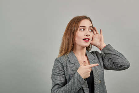 Eavesdropping, espionage, gossip, holding hand near head and looking away, what, relying on hand-ear listening the good news, trying to listen, cupping her ear. Young attractive woman, dressed jacket