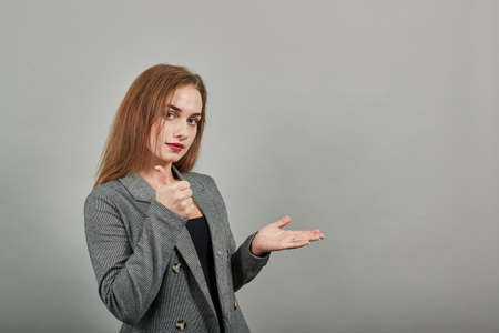 showing thumbs up, like sign Positive something good has happened finger gesture for fine result well done. Young attractive woman, dressed gray jacket, with green eyes, light brown hair, background
