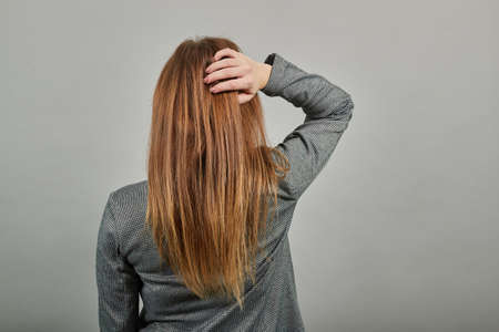 Posing with her back faced to camera, isolated over copy space background. A lovely stands. Standing. Young attractive woman, dressed gray jacket, with green eyes, light brown hair, background