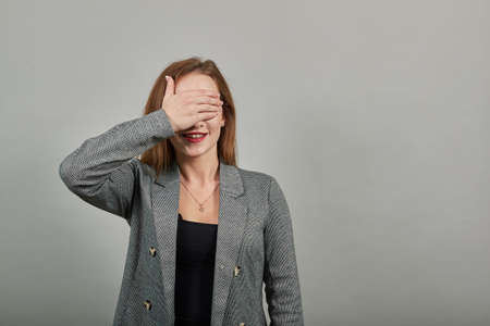Girl covered her face with hands in surprise. Caucasian woman covering eyes. Young attractive woman, dressed gray jacket, with green eyes, light brown hair, background