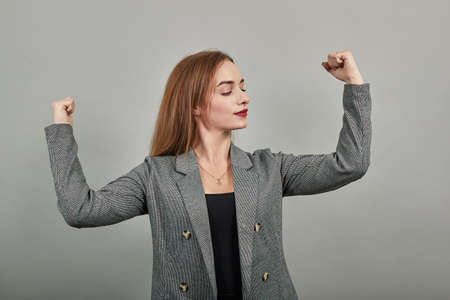 Feels proud have strength, shows great power, raises arms to show muscles confident in victory, looks strong and independent, flexing arm, facial expressions, feelings, attitude, life perception