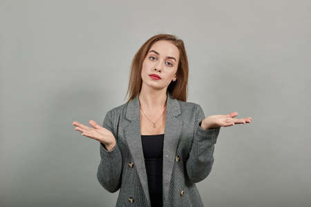 Young attractive woman, dressed gray jacket, with green eyes, light brown hair, background. Palms up, place your product here, raising arms wide spread is catching something.