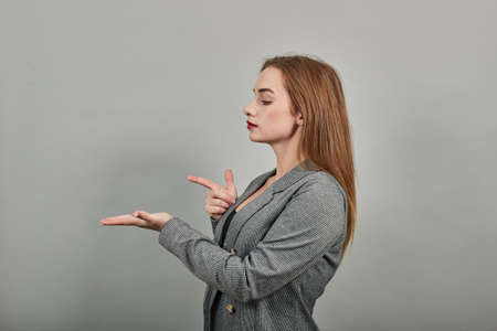 Palms up, place your product here, raising arms wide spread is catching something. Young attractive woman, dressed gray jacket, with green eyes, light brown hair, background