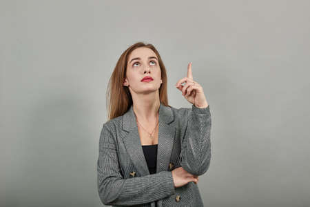 Hand points index finger up, pointing forefinger surprise gift option, great idea. Young attractive woman, dressed gray jacket, with green eyes, light brown hair, background