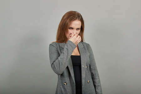 Covering nose with hand showing something stinks, isolated, hands face against, staring into camera, eyes wide open, two fingers. Pinches snout looks, disgust bad smell sign. Young attractive woman