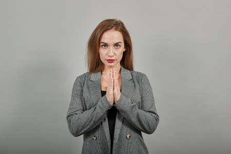 Folded hands together praying asking God for help ask implore wish upwards Jesus Christ. Young attractive woman, dressed gray jacket, with green eyes, light brown hair, background Stock fotó