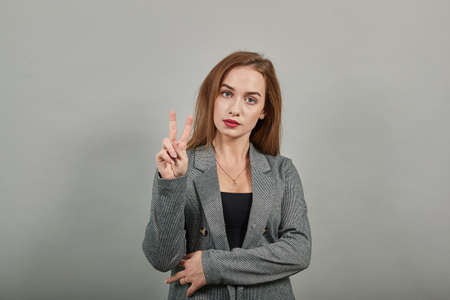Showing two 2 fingers hand gesture, show the number three with hands, pointing up arm while smiling confident, happy. Young attractive woman, dressed gray jacket, with green eyes, light brown hair