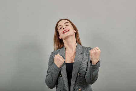 Arms up celebrating success fists in exultation. Young attractive woman, dressed gray jacket, with green eyes, light brown hair, background Stock fotó