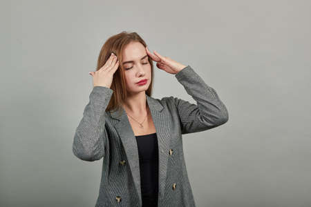 Headache grimacing pain holds the back of neck indicating location. Fatigue during workaholism labor. Young attractive woman, dressed gray jacket, with green eyes, light brown hair, background