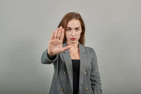 Palm arm raised air angry look straight you will not pass through facial expression harsh. Serious looking strict demands stop, pulls hand forward camera, says no, disagrees, frowns face, warning