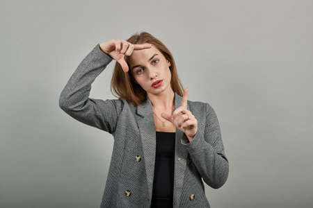 Hands making photo frame, fingers framing distance, photography sign made by human arm, framework formed, feeling happy, friendly and positive, smiling, portrait. Young attractive woman, gray jacket