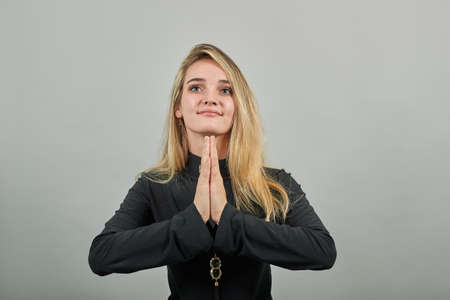 Folded hands together praying asking God for help ask implore wish upwards Jesus Christ. Young attractive woman, dressed black sweater with green eyes, blonde hair, background